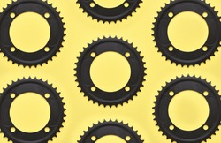 Bicycle sprockets pattern on yellow background, black mtb sprockets top view, flat lay.