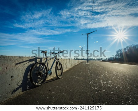 Bicycle stands at the side of the road on a sunny day, empty road, sun glare, blue sky, vignette
