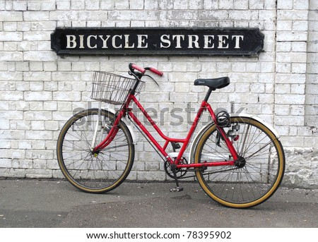 Bicycle Street sign with a red bicycle leaning against a white painted brick wall - stock photo
