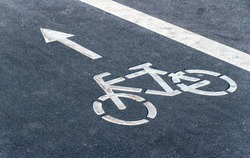 Bicycle symbol on a bike lane with directional arrow of movement. Bicycle lane for bike rider