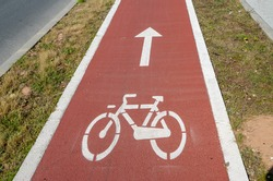 Bicycle symbol on red street, close up. Bicycle path in the city. Red bicycle lane. Bike or cycling lane sign. Urban traffic and transportation. Lifestyle.