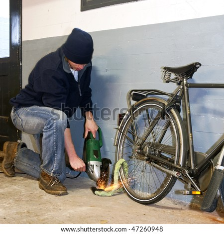 Bicycle thief busy breaking the lock with a portable grinding machine