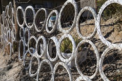 Bicycle tires roped up on link fence
