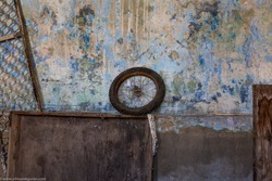 bicycle wheel standing against the wall in the ruined house