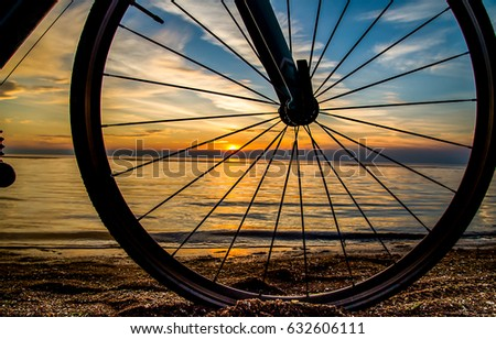 Bicycle wheel sunset beach #632606111