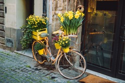Bicycle with a yellow flower basket next to a modern cafe