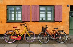 Bicycles in front of an orange house facace in Nyboder (historic row house district of former Naval barracks in Copenhagen, Denmark).