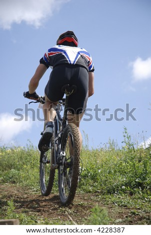 Bicyclist on a background blue sky - stock photo