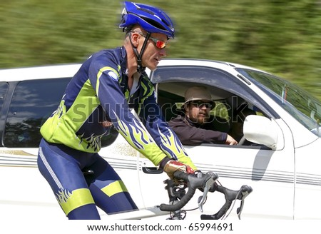 bicyclist overtakes a automobile