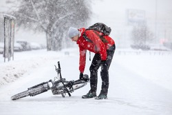 Bicyclist raises the fallen bike from slippery road after crash, person riding a bicycle in town at winter season