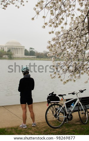 Bicyclist rests in front of Thomas Jefferson Memorial during cherry blossom festival in Washington DC United States