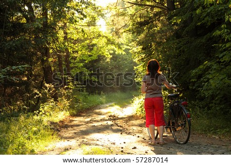 Bicyclist woman walk in the park with bikes - forest road