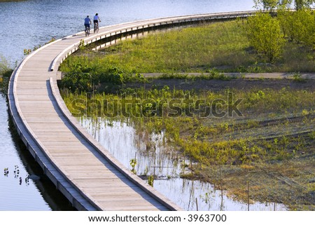 Bicyclists are riding along the boardwalk. Evening scene in a city park, Carmel, IN - stock photo
