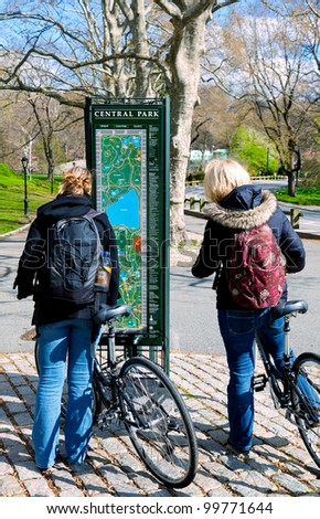 Bicyclists in Central Park, New York City, stop to check a map kiosk