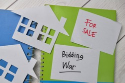 Bidding War and House For Sale write on sticky notes isolated on Office Desk