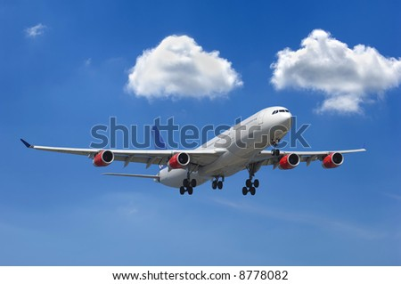 Big airliner and two white clouds on a blue sky