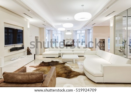 Big and comfortable living room with white interior in luxury mansion