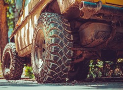 Big and dirty tires of an off-road car sitting on the street – Yellow monster truck with huge rubber wheels with a rough and detailed surface
