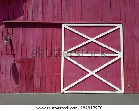Big and small doors on the wall of red wooden barn