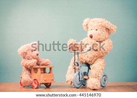 Big and small Teddy Bears on old retro toy bicycle and wooden car. Vintage instagram style filtered photo