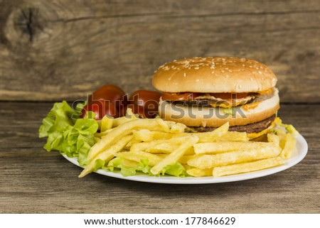 Big and tasty burger with fries, salad leaves and tomatoes on wooden background