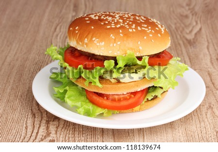 Big and tasty hamburger on plate on wooden table
