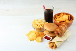 Big appetizing hamburger with fries and a coke and chips on white wood table