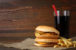 Big appetizing hamburger with fries and a coke on the fabric on a brown wooden table