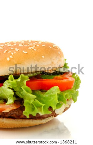 Big appetizing hamburger with vegetables close-up isolated junk food on white background side view