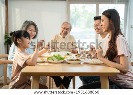 Big Asian happy family spend time having lunch on dinner table together. little kid daughter enjoy eating food with father, mother and grandparents. Multi-Generation relationship and activity in house