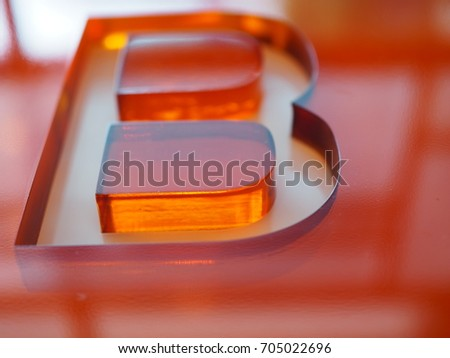 """Big """"B"""" letter shape groove engraved on red orange thick transparent acrylic glass, perspective shot with sunlight reflection from window"""