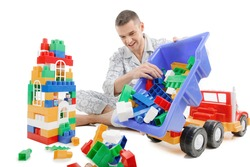 Big baby. Excited young man in pajamas playing toys while isolated on white