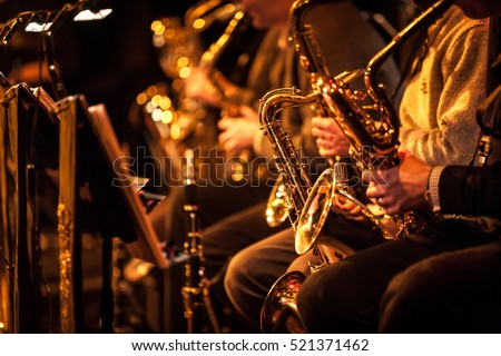 Big Band saxophone section. Candid view of a row of saxophone players in mid performance during a big band rehearsal.