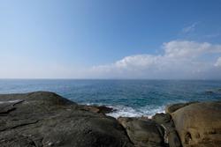 big bare stony land before blue sea horizon and white cloudy sunny sky