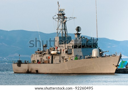 Big battle ship in the dock against blue sky and mountains