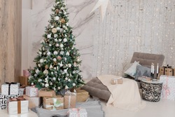 Big beautiful New Year tree with gifts in a white decorated hall for the New Year