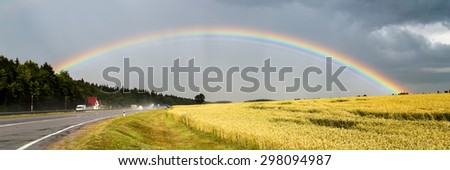 Big beautiful rainbow over highway and cereals field  letterbox view. Rainy day panorama