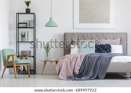 Big bed with cute pastel bedding in woman's room