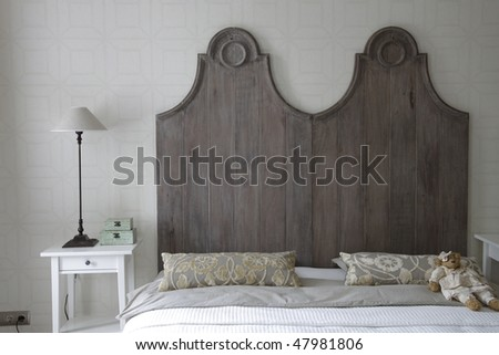 big bed with high headboard in gray color