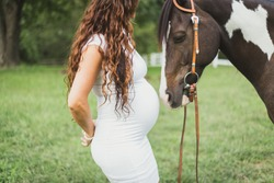 Big belly pregnant woman with horse