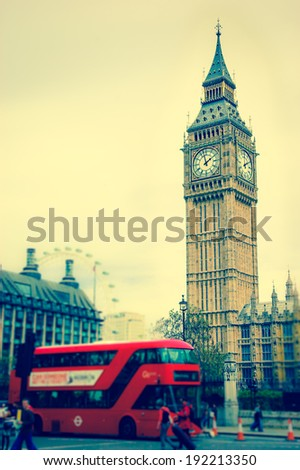 Big Ben and blurred red double decker bus, tourists and London Eye. (London, UK). Aged photo.