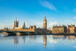 Big Ben and Westminster parliament with colorful sky and water reflection