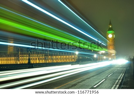 Big Ben at night along with the lights of the cars passing by