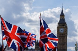 Big Ben at the Palace of Westminster with Union Jack flags in the foreground in London England United Kingdom UK