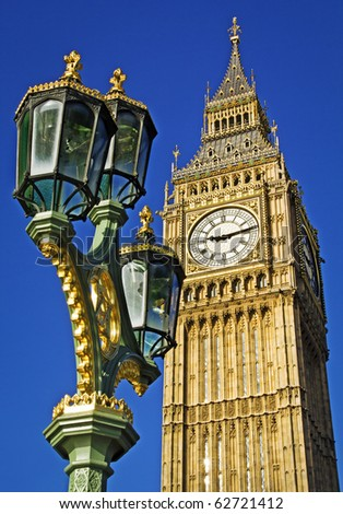 Big Ben seen from Westminster Bridge with an ornate lamp post in the foreground. Clear summer sky.