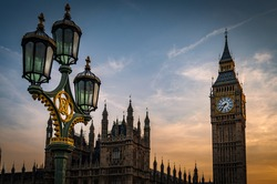 Big Ben, The Houses of Parliament and a lamppost from the Westminster bridge at sunset on a cloudy summer evening in London, England, UK