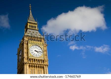 Big Ben, Westminster, London. Clock tower under a blue sky with a fluffy cloud