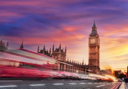 Big Ben with red bus against colorful sunset in London, England, UK