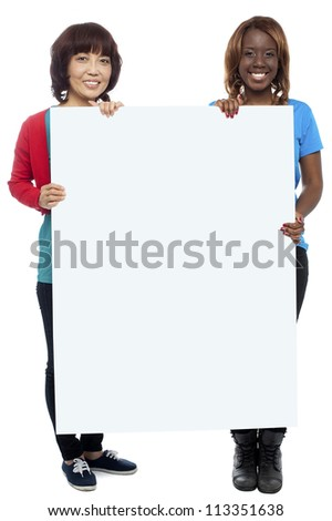 Big billboard presented by casual girls. Full length shots on white background