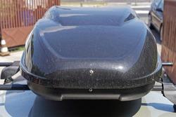 Big black aerodynamic box at car roof front